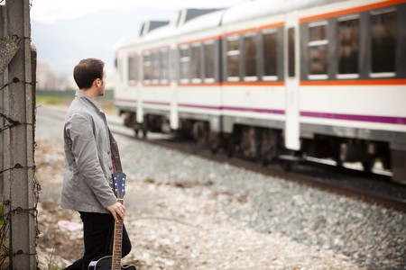 Lone musician looking at a train passing by. Stock Photo - 6965719