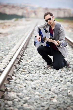 Young handsome musician playing his blue guitar. photo