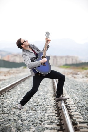 man playing guitar: Young handsome musician singing outdoors.