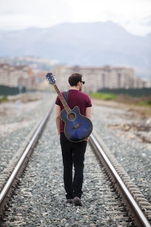 railroad: Young male musician walking with his acustic guitar.