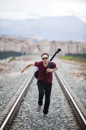running late: Young male musician running on railway road. Stock Photo