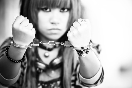 Young asian girl showing handcuffs on her wrists photo