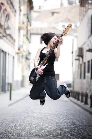 spigola: Giovane ragazza giocando il suo basso elettrico di citt�