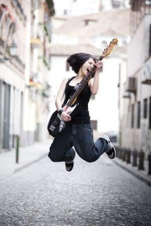 Young girl playing her electric bass in the middle of the city Фото со стока