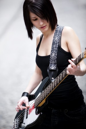 Dark haired beautiful girl playing her electric bass. photo
