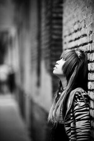 emo: Young thoughtful  asian against urban wall