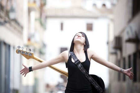 bass guitar women: Young beautiful guitar performer with raised arms.