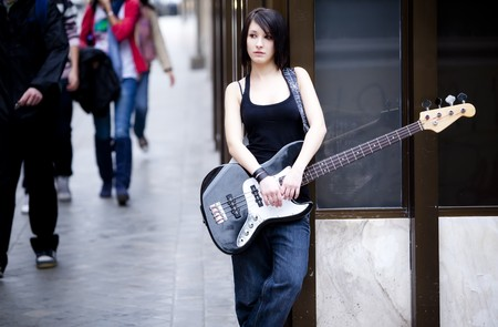 Street female musician with her electric bass photo