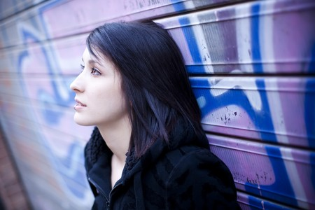 dark haired woman: Young beautiful teen in pensive gesture in street background. Stock Photo