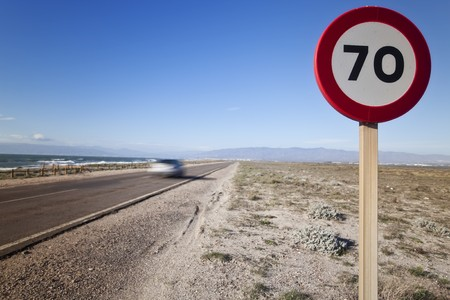 Speed sign in a road in the middle of the desert. photo