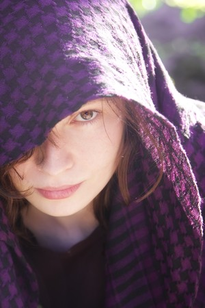 middle eastern clothing: Staring woman portrait covered by violet veil Stock Photo