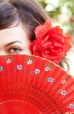 Spanish woman behind traditional fan. photo