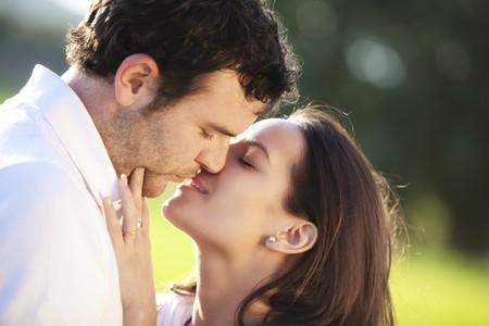 beso: Joven pareja mostrando su amor al aire libre. Foto de archivo