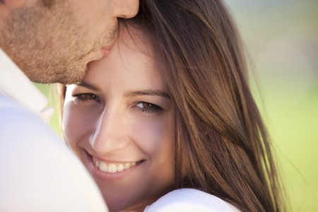 Young beautiful girl staring at camera while being kissed Stock Photo - 7043234
