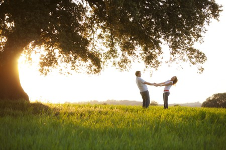 tree silhouettes: Young playful couple under huge tree at sunset