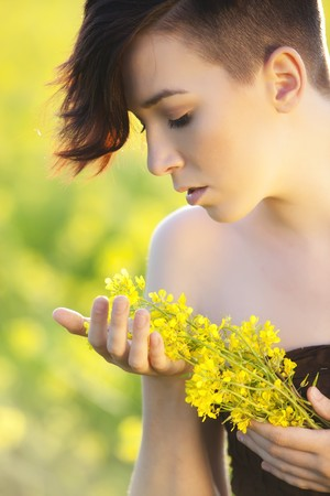Young girl portrait holding yellow flowers photo