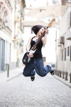 femme avec guitare: Joyeuse jeune femme jouant une guitare � la rue.