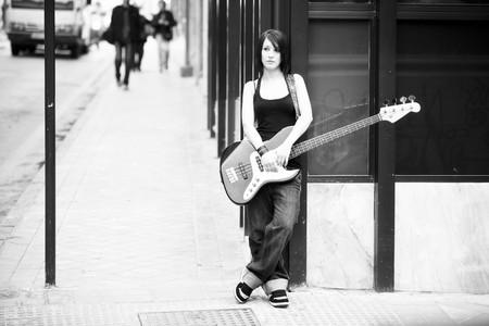 Junge schönen weiblichen Gitarrist in Schwarz und weiß
