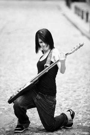 bass guitar women: Joyful young woman playing a guitar at the street