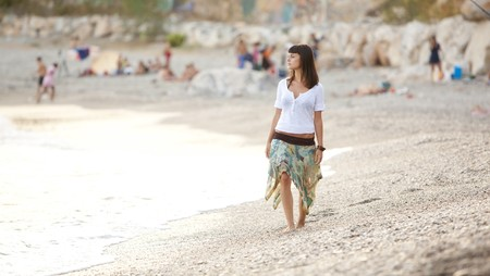 Young beautiful lone girl walking on a crowded beach. photo