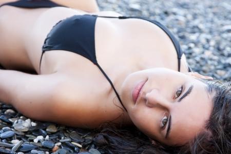 Laying beauty wearing black small bikini. photo
