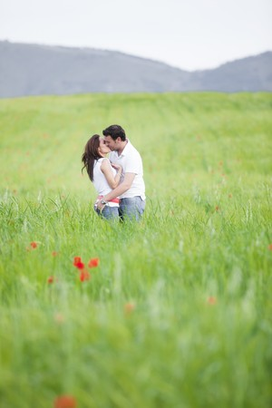 Young couple kissing on green field Stock Photo - 7491540