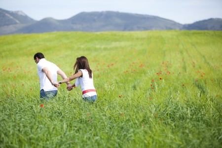 Young couple walking through green field. Standard-Bild