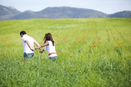 exploring: Young couple walking through green field. Stock Photo
