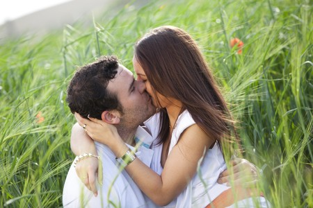 Young casual kissing couple on a wheat field.