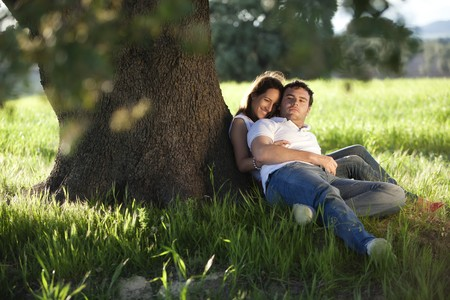 Young beautiful couple under tree.