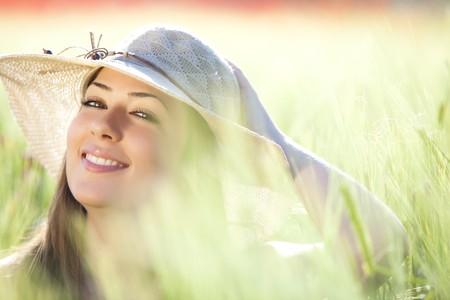 Young beautiful Girl mit Hut Kamera unter Grün Weizen, Fokus auf dem rechten Auge starrte. Lizenzfreie Bilder