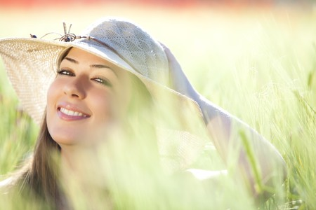 feeling: Young beautiful girl with hat staring at camera among green wheat, focus on the right eye.