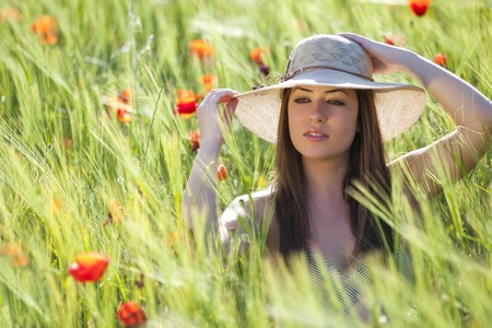 poppy flower: Young girl portraiting elegance on a green field.