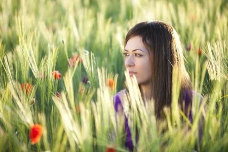 Young beautiful girl posing in a green field. photo