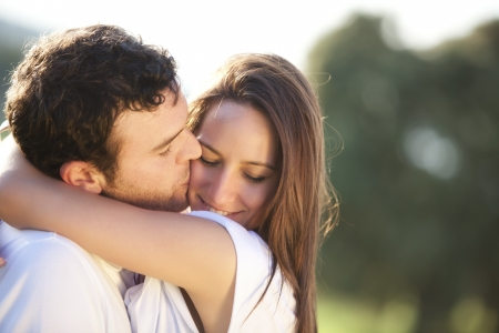 Young beautiful couple in a sweet cheek kiss photo