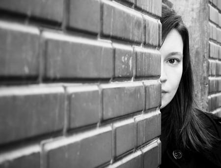 Woman looking behind a brick wall. photo