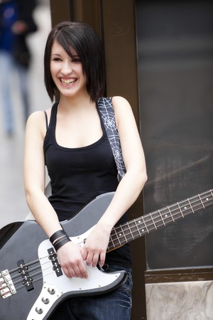 bass guitar women: Young cheerful female guitarist on urban background Stock Photo