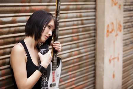 Young female guitarist on urban background photo