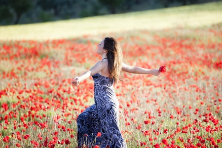 Young beautiful girl running on poppies field. photo