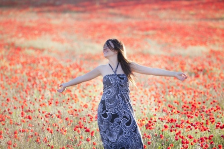 Young beautiful woman with raised arms on a poppies field. photo
