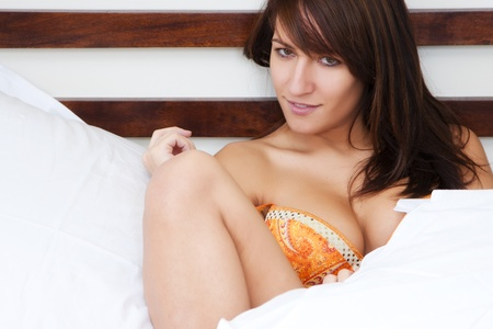 Sensual young woman staring at camera from bed.