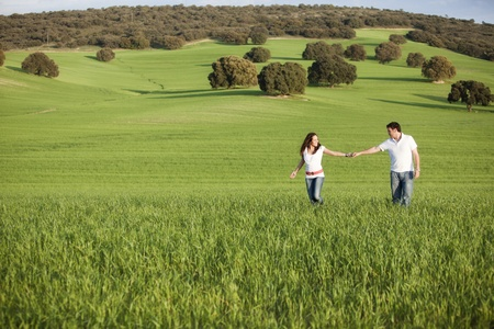 Young beautiful couple hand by hand on natural background.