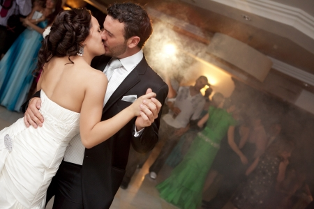 Kissing just married couple dancing in front of their unrecognizable friends.