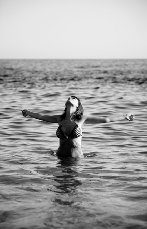 Young beautiful girl with raised arms on the ocean. photo