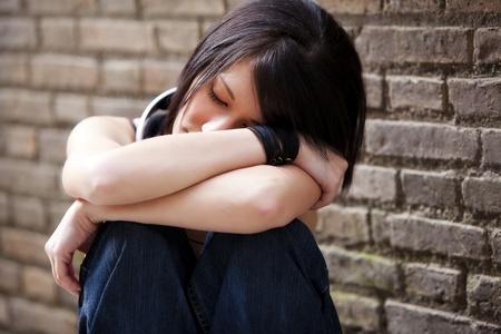 ojos tristes: Young hermoso hab�a cerrado a chica de ojo en segundo plano urbano. Foto de archivo