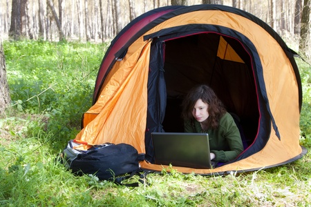 Young woman using laptop in the middle of the forest photo