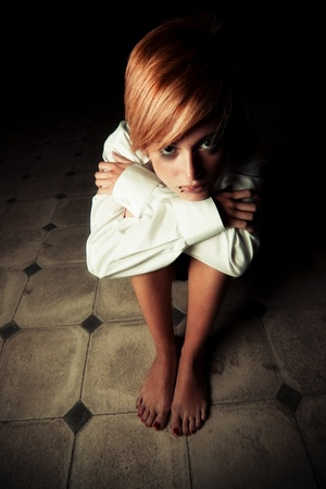 Young blond woman alone in the darkness photo