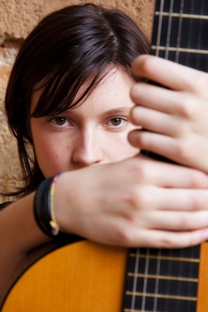 Woman holding guitar, focus on face. photo