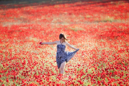 Young beautiful girl running on poppies field. Stock Photo
