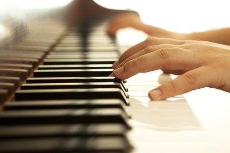 piano: Manos sobre el piano en tonos c�lidos. Foto de archivo